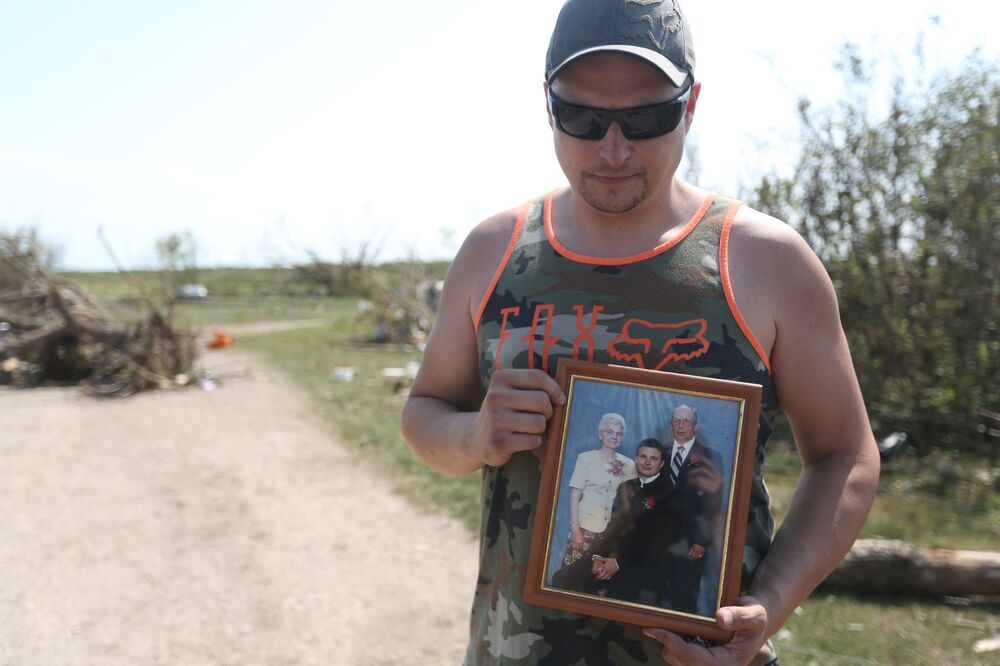 Kelly Brown holds a photo of himself with his grandparents outside of his grandfathers former home. Seventy-seven-year-old Jack Furrie was killed in a tornado on Friday evening. (Melissa Verge / The Brandon Sun)