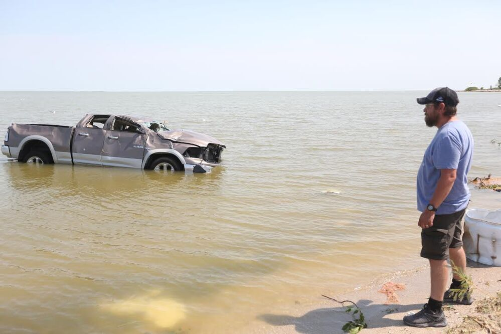 Shawn Gurke, a resident of Alonsa, watched a truck floating in Lake Manitoba after a tornado hit on Friday.  (Melissa Verge / The Brandon Sun) -