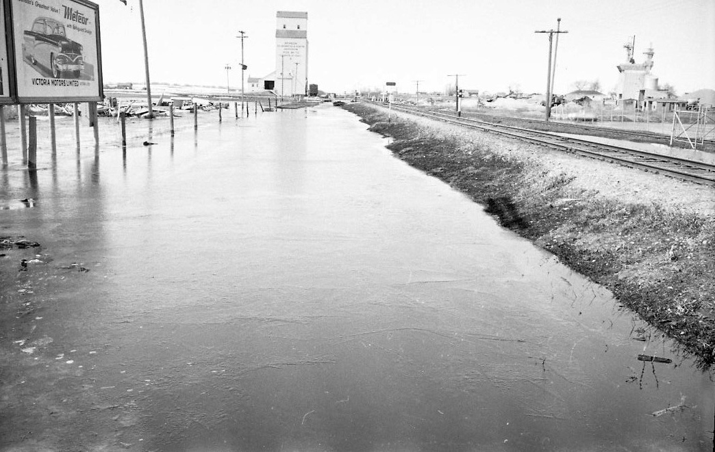 Do you recognize the location of this photo, taken during the flood of 1954? Some people think it shows the railway near Pacific Avenue, others point to the railway near Park Avenue. (Courtesy CKX fonds; S.J. McKee Archives; Brandon University)