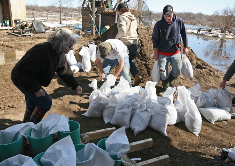 Volunteers work to place sandbags around a home in the Rural Municipality of Cornwallis to protect against rising river levels, Tuesday afternoon. (Colin Corneau/Brandon Sun)