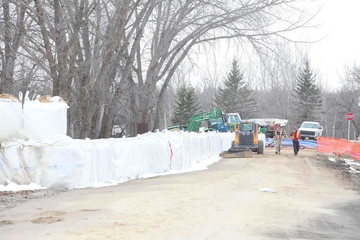 Sandbags create a dike along the campground road in Spruce Woods Provincial Park at the edge of the swollen Assiniboine River on Monday. Workers were busy on Monday fighting the floodwaters at the Seton Bridge where Highway 5 crosses the Assiniboine in the park. (Tim Smith/Brandon Sun)