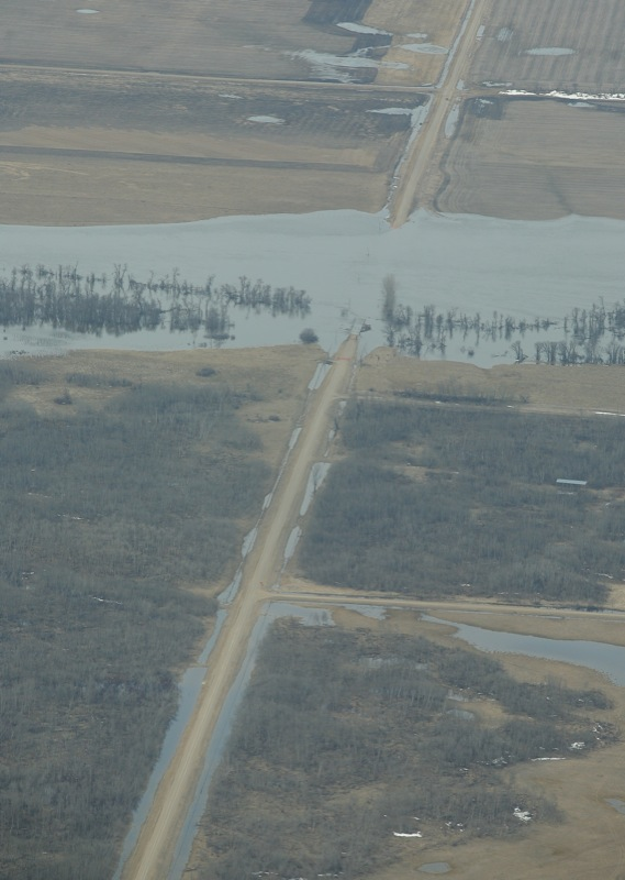 A gravel road is consumed by the flood waters from the Souris River west of the town of Hartney, Man., on April 21, 2011.