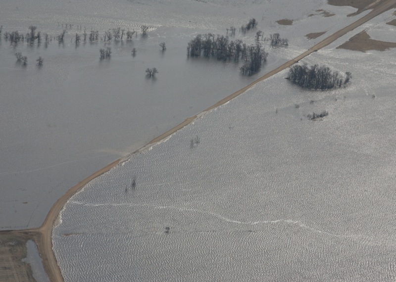 The swollen Souris River floods a large area, including a pump house building, by the Maple Grove Hutterite Colony west of Hartney, Man., on April 21, 2011.