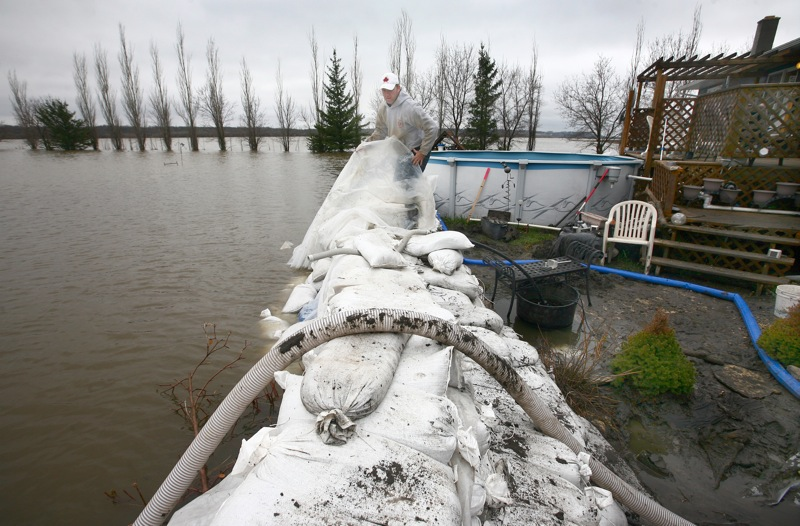 Conrad Winters wraps a sheet of plastic over the top of a sandbag ring-dike protecting his uncle's home along Grand Valley Road on Tuesday morning.
