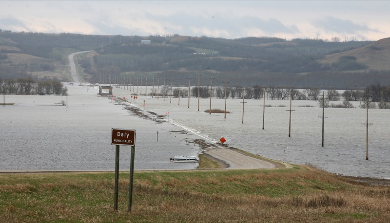 The swollen Assiniboine River covers the valley floor consuming the bridge on Highway 250 west of Brandon on Tuesday. (Bruce Bumstead/Brandon Sun)