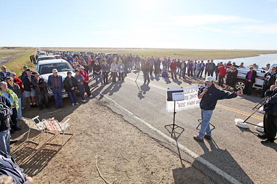 About 200 people gather to listen to speakers during a rally on the east side of the washed-out Highway 251 bridge over the Souris River east of Coulter on Tuesday. Area residents, farmers and workers are demanding the party that forms the next provincial government on Oct. 4 act quickly to fix the bridge.