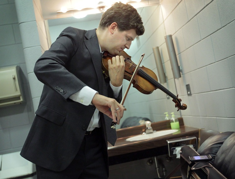 Violinist James Ehnes practices on his Stradivarius violin as he watches a Detroit Tigers baseball game on his smartphone before a Brandon concert. (Colin Corneau/Brandon Sun)