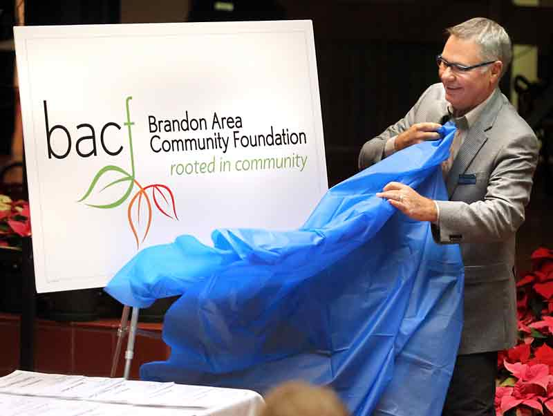 Phil Weiss unveils the new logo of the Brandon Area Community Foundation during the philanthropic group's 21st annual grant presentation ceremony at city hall on Wednesday evening.