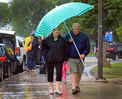 Elaine Linton and Harry Knight take cover under a beach umbrella from a pelting rainstorm, Saturday afternoon in Wasagaming. The storm system didn't stop events in the resort village but did delay the final of the annual Tamarack golf tournament.