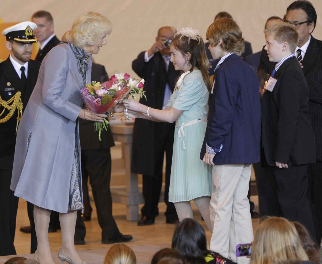 Camilla, Duchess of Cornwall receives flowers from Avery Good, Ethan Enns and Ryan Petricig, three grade six scientists from Brant Argyle School in Argyle, MB. at the ceremony in the Stevenson Hangar Wednesday morning. Their  science experiment was sent to the international Space Station to study how to protect astronauts from cancer caused by radiation.      (Wayne Glowacki / Winnipeg Free Press)