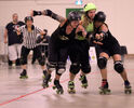 Kristin (Holey Mow-zes!) Shukin of Gang Green tries to break her way through Dolly Hardon (left) and Pipe'r of Pile O' Bones on Saturday as the two teams met for a bout in Shilo. Shukin scored four points in the dying seconds of the game in her team's 152-150 victory.