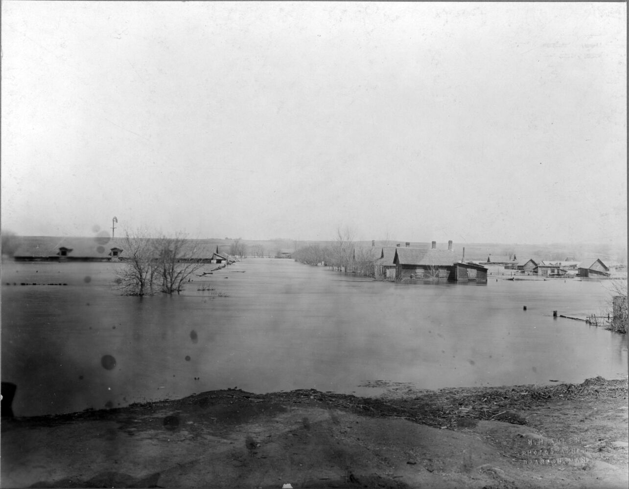 """An image of houses on the Assiboine floodplane (Brandon's """"flats"""") submerged in flood-waters. The """"flats"""" refers to the Assiniboine River floodplane from 18th Street to First Street on either side of the river. See p. 223 of G.F. Barker's Brandon: A City for a description of the 1922 flood.  (H.H. Allen image, BAPC, S.J. McKee Archives)"""
