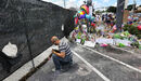 A visitor kneels at a memorial in front of the Pulse nightclub in Orlando, Fla.