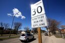Vehicles pass through a school zone on 26th St. in front of J.R. Reid School in this file photo from April. Drivers will again have to reduce their speed in these areas on Sept. 1. (File)