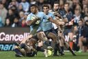 Waratahs' Kurtley Beale is tackled by the Brumbies' Pat McCabe during their Super Rugby semifinal match in Sydney Saturday, July 26, 2014. (AP Photo/Rob Griffith)