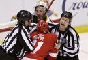 Linesmen Scott Driscoll, left, and Mark Shewchyk (92) separate Detroit Red Wings left wing Tomas Tatar (21) of the Czech Republic and Boston Bruins left wing Brad Marchand during the third period of Game 3 of a first-round NHL hockey playoff series in Detroit, Tuesday, April 22, 2014. (AP Photo/Carlos Osorio)