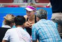Eugenie Bouchard of Canada, center, talks with medical staff before retiring from her first round match against Andrea Petkovic of Germany at the China Open tennis tournament at the National Tennis Stadium in Beijing, Monday, Oct. 5, 2015. (AP Photo/Andy Wong)
