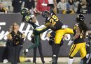 Edmonton Eskimos' Fred Stamps, left, leaps to catch a touchdown in front of Hamilton Tiger-Cats' Ed Gainey during second half CFL action in Hamilton, Ont. on Saturday, September 20, 2014. THE CANADIAN PRESS/Darren Calabrese