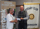 Bernie Chrisp, chairman of 55 Plus Games host committee, presents a cheque to Cheryl Winger, president of the Rotary Club of Brandon No. 1344.