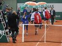 Belgium's David Goffin, rear right, and Latvia's Ernests Gulbis, center right, leave as rain suspended the fourth round match of the French Open tennis tournament at the Roland Garros stadium in Paris, France, Tuesday, May 31, 2016. (AP Photo/Alastair Grant)