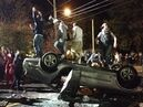 People stand atop an overturned car in Keene, N.H. on Saturday, Oct. 18, 2014, during a night of violent parties that led to destruction, dozens of arrests and multiple injuries, near the city's annual pumpkin festival. The parties around the school coincided with the annual Keene Pumpkin Festival, where the community tries to set a world record of the largest number of carved and lighted jack-o-lanterns in one place. (AP Photo/The Boston Globe, Jeremy Fox) BOSTON HERALD OUT, QUINCY OUT; NO SALES