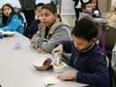 In this Wednesday, April 8, 2015 photo, students are served breakfast at the Stanley Mosk Elementary School in Los Angeles. In this Los Angeles Unified School District program, and in other major urban school districts, breakfast is increasingly being served inside the classroom. The number of breakfasts served in the nation's schools has doubled in the last two decades, a surge driven largely by a change in how districts deliver the food. Instead of providing low-income students free or reduced-price meals in the cafeteria, they're increasingly serving all children in the classroom. (AP Photo/Nick Ut)