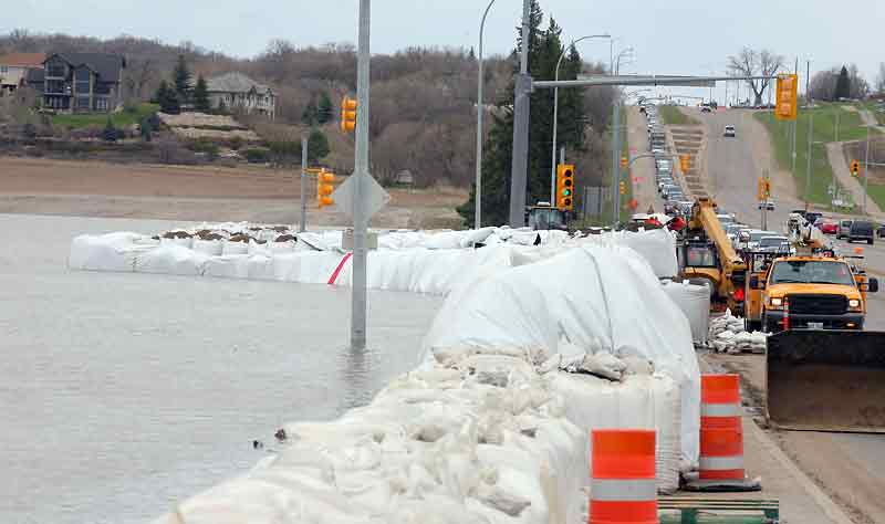 In this May 2011 photo, provincial highway crews work to shore up the super sandbag dike at the intersection of Grand Valley Road and 18th Street as the city prepares for higher floodwaters on the Assiniboine River. The city should escape flooding this year.