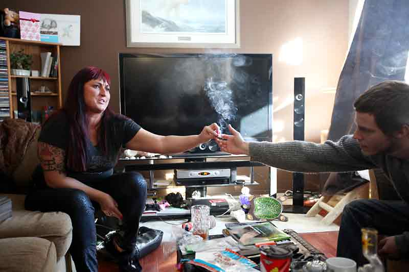 Jade Ridge, CEO and founder of the Canadian Medical Marijuana Clinic, shares a joint with fellow medicinal marijuana user Doug Affleck in the living room of her home in Brandon.