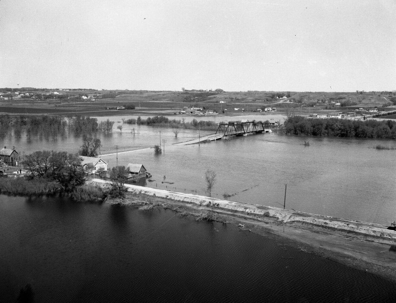 The 18th Street bridge is dry, but all accesses are flooded out during this look at the 1954 Assiniboine River flood. Although the road in the foreground, which looks to be John Avenue, it doesn't appear to have served as an effective dike. (Courtesy CKX fonds, S.J. McKee Archives, Brandon University)