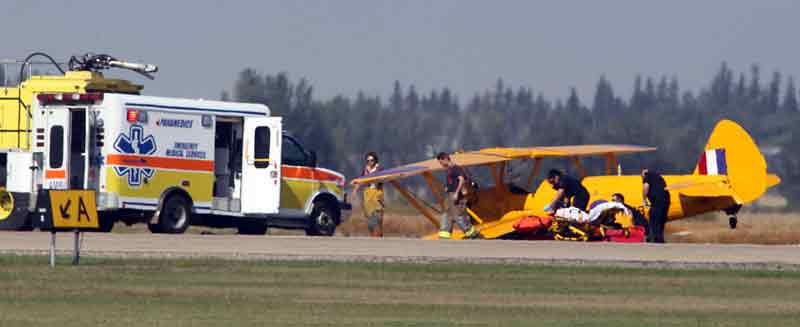 Emergency crews work to stabilize a passenger from a vintage biplane that crashed on takeoff at the Brandon Municipal Airport over the noon hour on Tuesday.