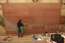 Colleen Granger paints one of the three backdrops used in the production of