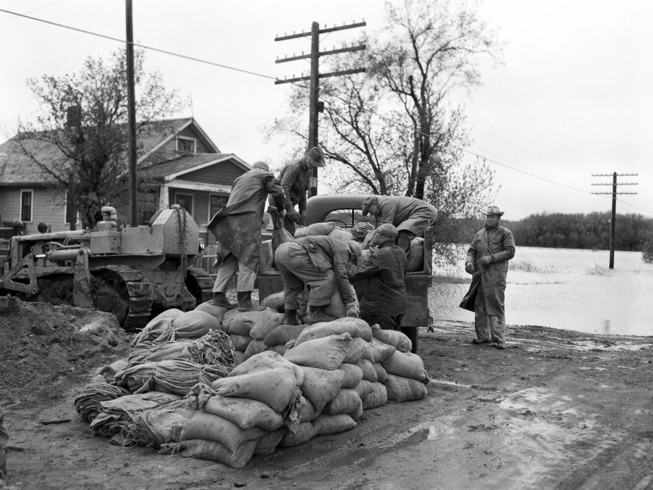 Workers load sandbags into a truck to fight the 1954 flood. (Courtesy CKX fonds; S.J. McKee Archives; Brandon University)