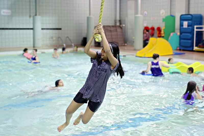 Grade 5 student Judith Martinez swings on the rope at the Sportsplex on Tuesday.