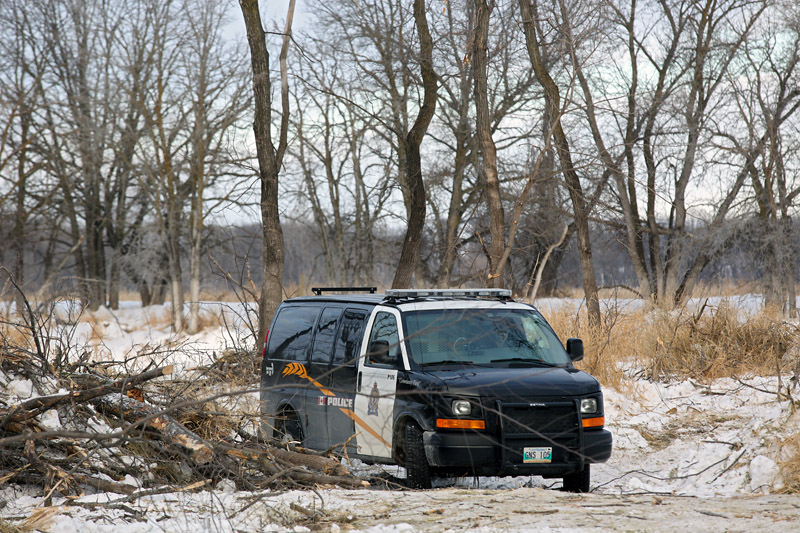 A Brandon Police Service member sits in a vehicle near the banks of the Assiniboine River in Queen Elizabeth Park on Wednesday morning. City police confirm that they're investigating after human remains were found in Queen Elizabeth Park on Tuesday evening.