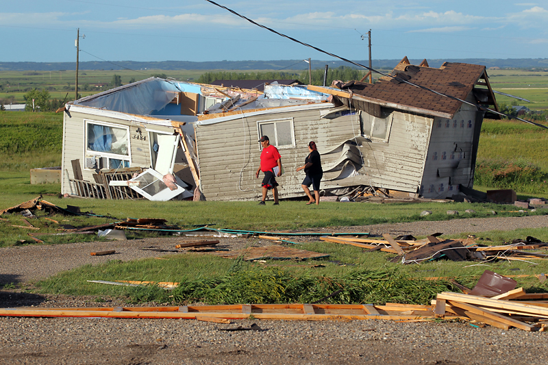 Sioux Valley Dakota Nation residents walk past a home that was blown off its foundation by a tornado last July. Nearly a year later, some homes damaged in the storm still don't have shingles, a local resident says.