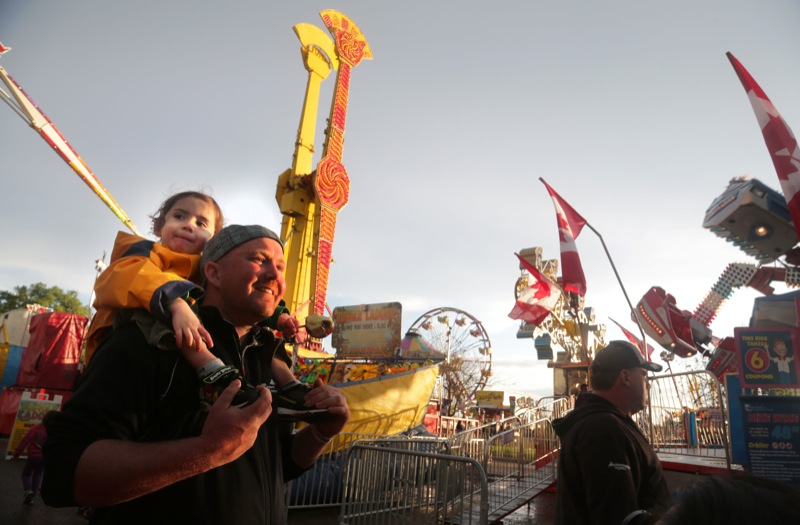 Paul Fowell holds his son Ethan aloft as the rainclouds break and the sun sets on the midway during the first night of the Manitoba Summer Fair, Wednesday evening at the Keystone Centre.