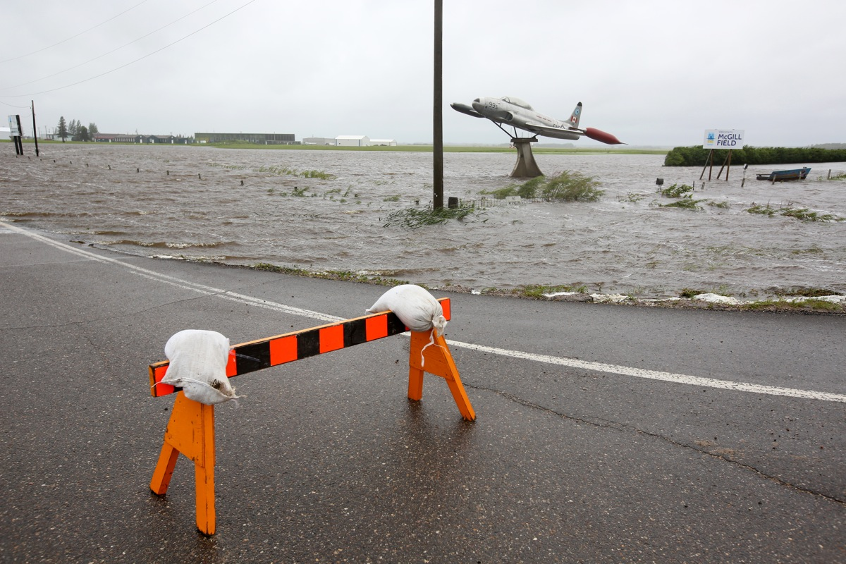 Overland flooding surrounds a T33 fighter jet on display along Highway 10 and Sandison Road near the Brandon Municipal Airport on Sunday after rain fell almost non-stop throughout the weekend. The airport was closed due to the flooding.  (Tim Smith/Brandon Sun)