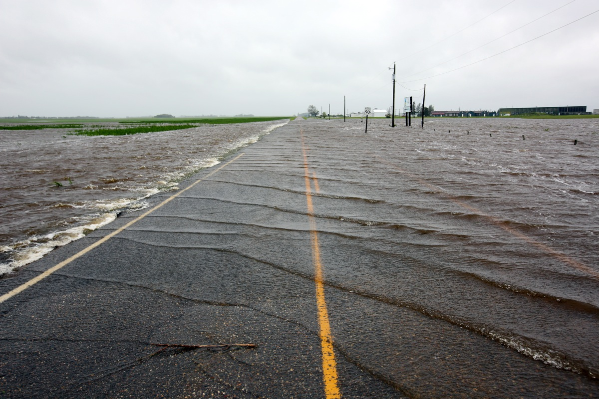 Overland flooding spills over Sandison Road near the Brandon Municipal Airport on Sunday after rain fell almost non-stop throughout the weekend. The airport was closed due to the flooding.  (Tim Smith/Brandon Sun)