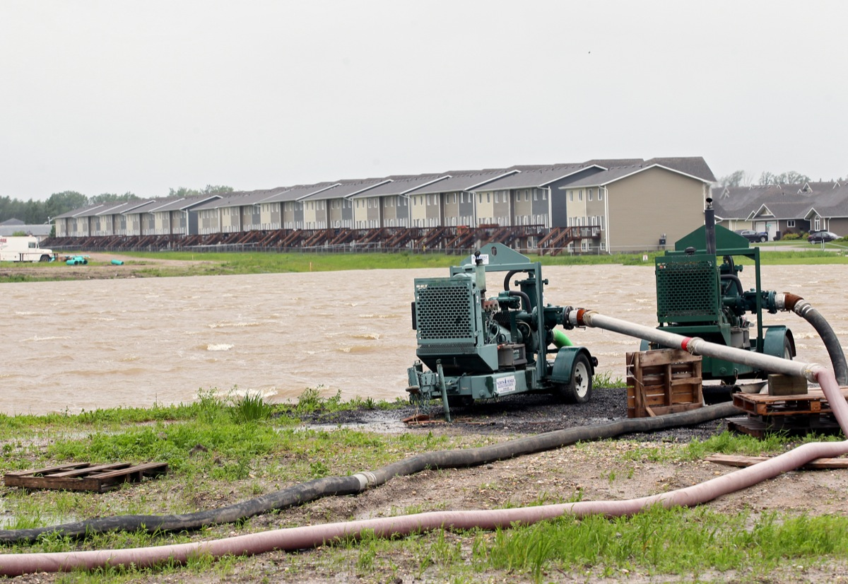 Water is pumped from a field on First Street south of Crocus Plains Regional Secondary School in Brandon on Sunday after excessive rainfall over the weekend.  (Tim Smith/Brandon Sun)