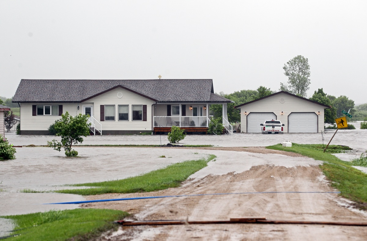 Flood water surrounds a home in the village of Cromer in southwestern Manitoba on Sunday after incessant rainfall over the weekend caused flooding forcing the evacuation of approximately 30 residents.   (Tim Smith/Brandon Sun)