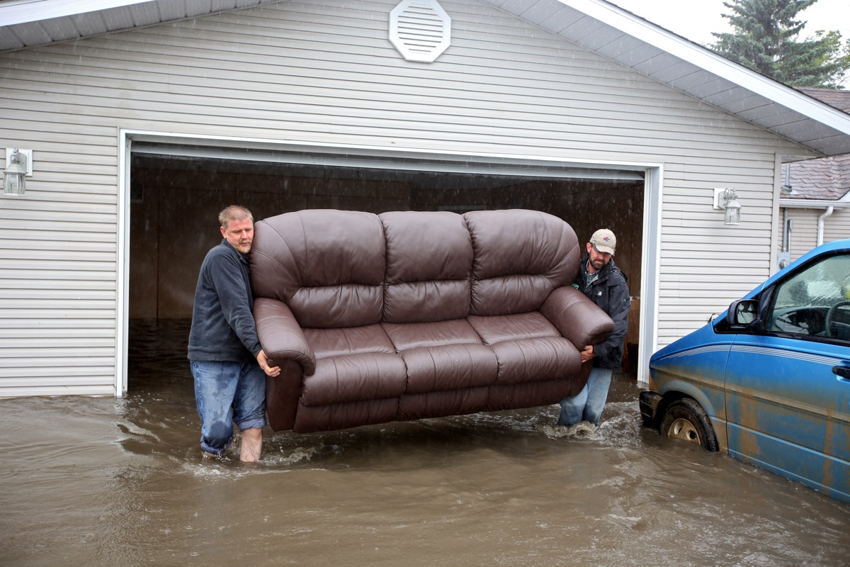 A Mr. Froese (no first name given) and Ivan Penner carry a couch from the flooded home of Greg and Amy Baerg to a waiting trailer in the village of Cromer in southwestern Manitoba on Sunday after flood water inundated several homes in the small community and forced the evacuation of approximately 30 residents.   (Tim Smith/Brandon Sun)