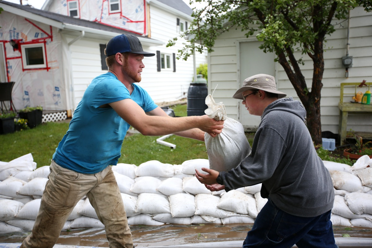Blair Bartel passes a sandbag to Jayson Brockman while the two volunteers help build a sandbag dike around homes in the town of Reston in southwestern Manitoba on Sunday after incessant rainfall creating overland flooding in the community. Reston was hit hard by flooding just over a year ago. (Tim Smith/Brandon Sun)