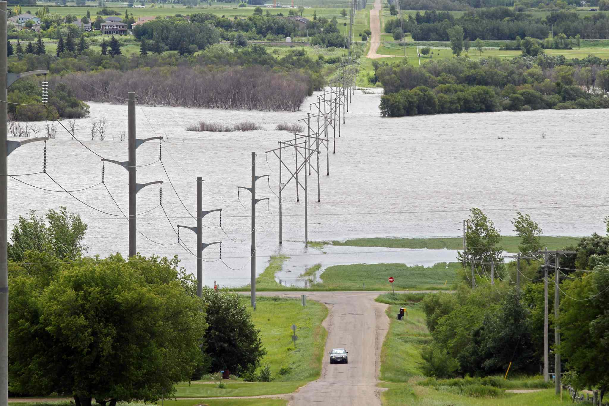 Water from the Assiniboine River covers farmland bordering Brandon's Grand Valley Road on Sunday afternoon.