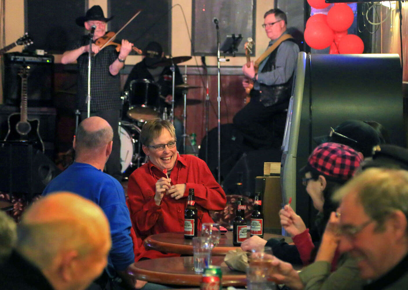 Friends share a laugh as a country band performs in the background. (Colin Corneau)