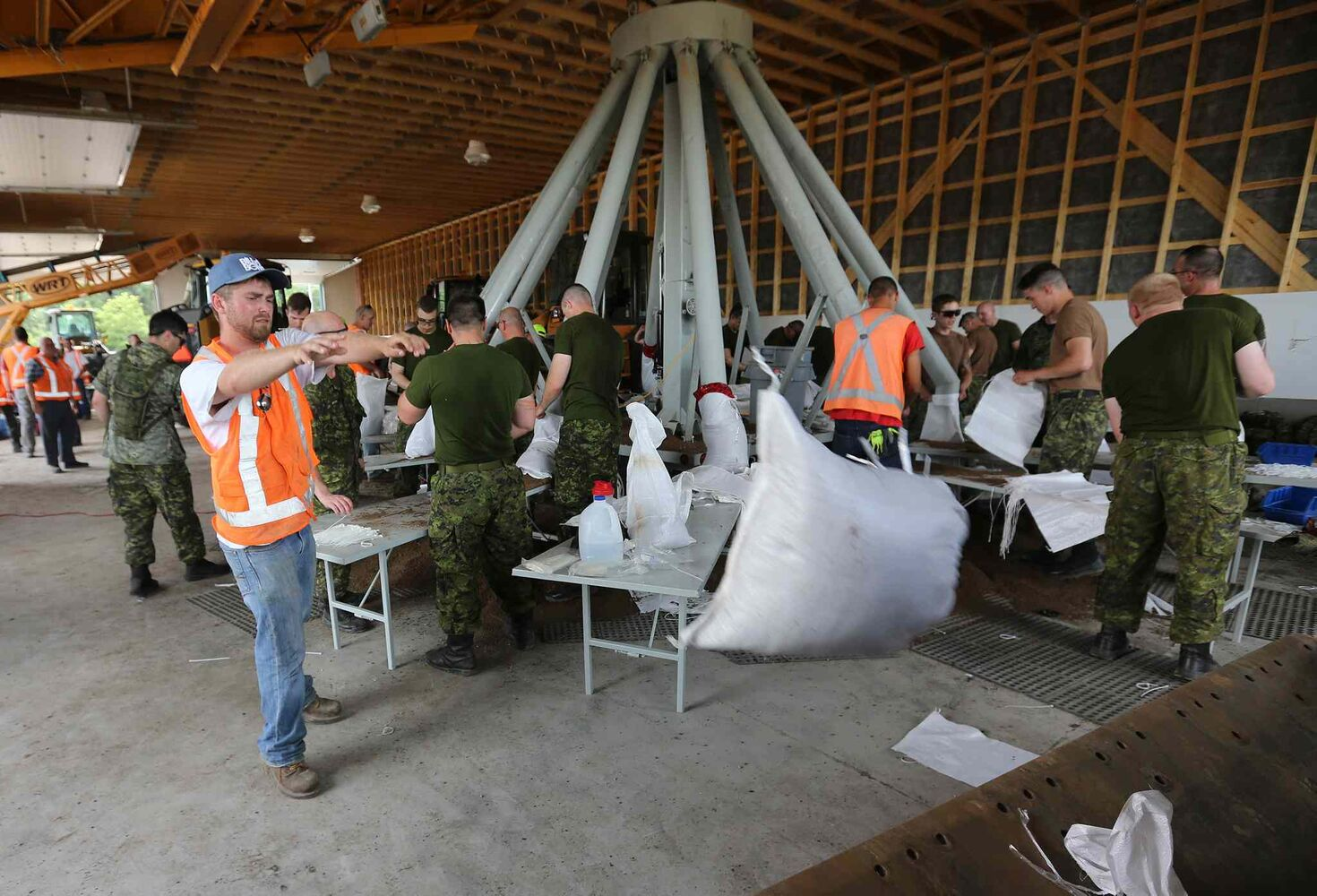 Soldiers from CFB Shilo and workers from the Municipality of Portage la Prairie work to make sandbags at the Portage Yard on Saturday. (TREVOR HAGAN/WINNIPEG FREE PRESS)