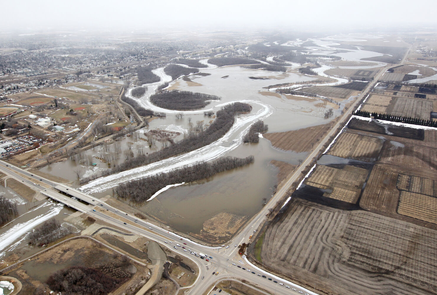The ice covered Assiniboine River that has flooded its banks into surrounding fields and parks is seen west of the intersection of 18th St. and Grand Valley Rd. (bottom section) on Friday. The flooding has extended to Grand Valley Rd. at 18th St. but would still have to rise quite a bit to flood the road. (Tim Smith/Brandon Sun)