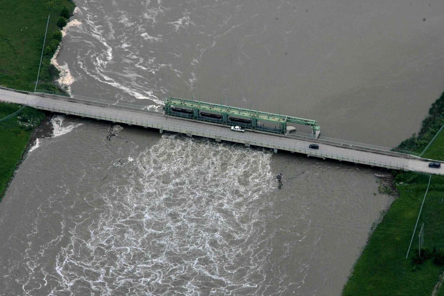 Heavy rains in western Manitoba and Saskatchewan recently have raised the level of the Assiniboine River, causing it to overflow its banks, flooding roads and farmers' fields. Aerial photo of bridge over the  Portage diversion dam just west of town where water is diverted north to Lake Manitoba.    (RUTH BONNEVILLE / WINNIPEG FREE PRESS)