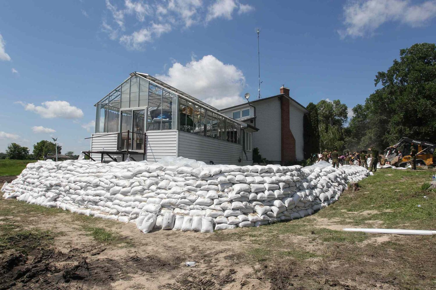 Kevin Van Camp's home with its protective sandbag walls near St. Francois Xavier Sunday afternoon.  (Mike Deal / Winnipeg Free Press)