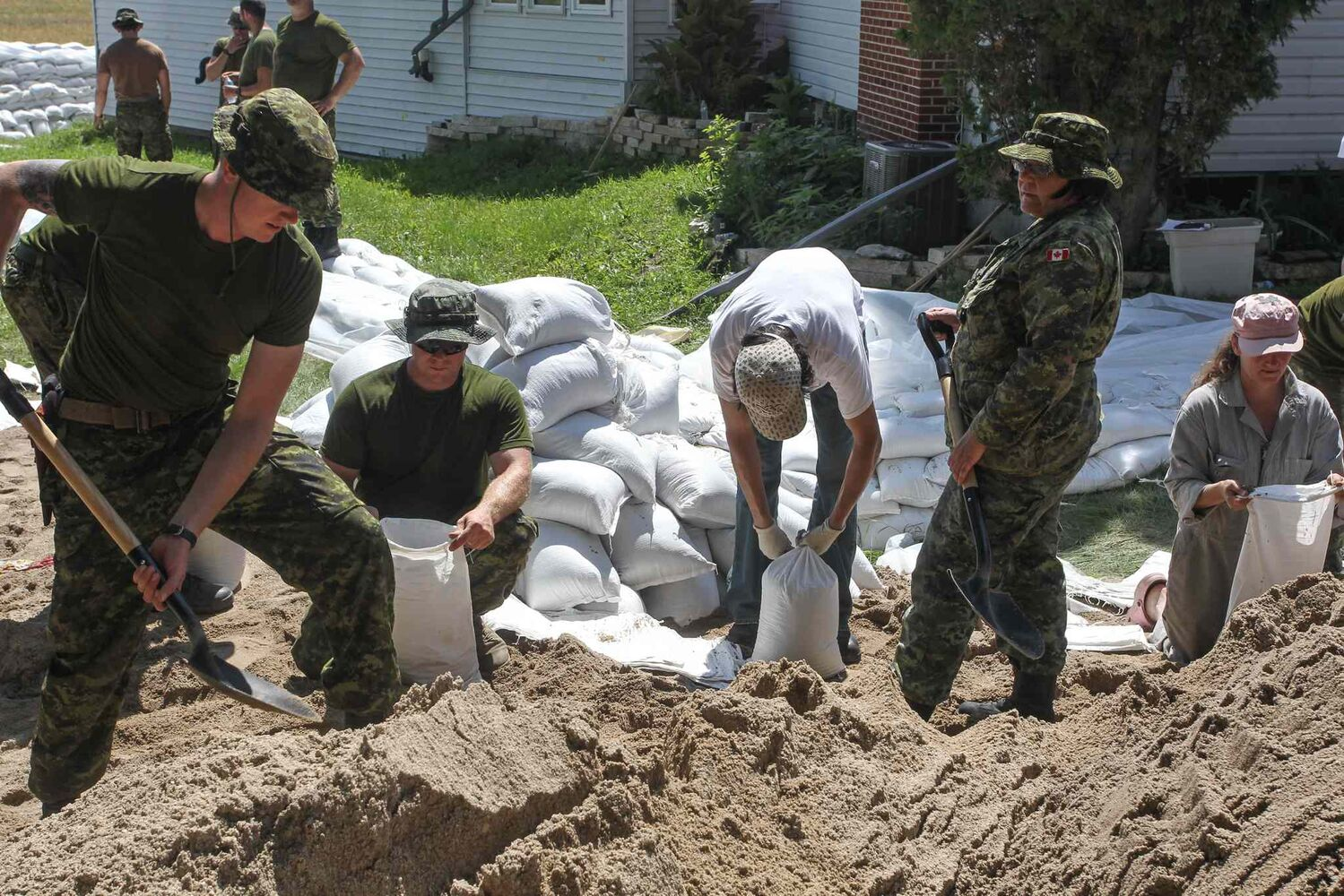 Soldiers from CFB Shilo and volunteers help fortify Kevin Van Camp's home from flood water near St. Francois Xavier Sunday afternoon.  (Mike Deal / Winnipeg Free Press)