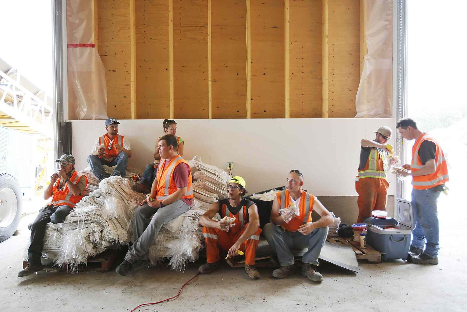 A provincial crew take a break after filling and loading sandbags in 30C temperatures in Portage la Prairie, Man. Saturday. (John Woods / The Canadian Press)